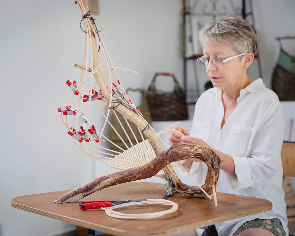 Pascale Germain - Artisan vannier en train de réaliser un panier en osier dans son atelier Saulée Vannerie