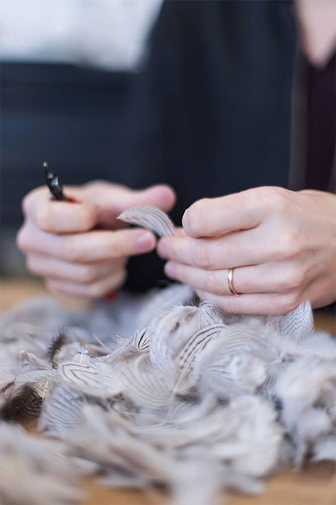 Geste de coupe de plumes blanches rayées noires par la plumassière parisienne Plumavera